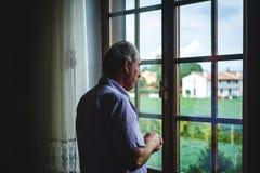 Trévise, Italie - 20 octobre 2018 : vieil homme seul regardant hors de la fenêtre pendant le jour d'hiver avec l'expression série photo libre de droits