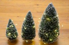 Três árvores de Natal pequenas da decoração da tabela Fotos de Stock