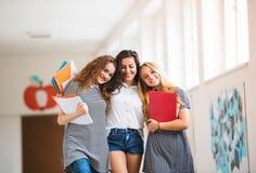 Três adolescentes no salão da High School durante a ruptura fotografia de stock