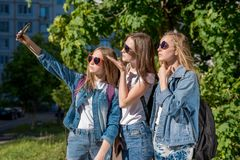 Três adolescentes no verão fora Faz uma foto da pessoa no telefone Vestem a roupa à moda das calças de brim ensolarado Foto de Stock Royalty Free