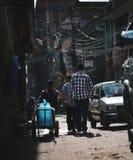 Três adolescentes que passam pela rua estreita de Thamel Imagem de Stock