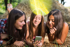 Três adolescentes que usam o telefone fora fotografia de stock royalty free