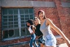 Três adultos novos que andam junto tendo o divertimento imagem de stock