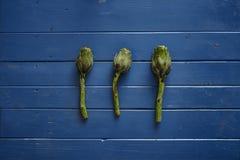 Três alcachofras frescas na tabela de madeira azul Imagem de Stock Royalty Free