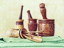 Três almofarizes de madeira com pilões e um frasco de madeira virado com cutelaria estão em uma toalha de mesa verde ou em um gua imagem de stock royalty free