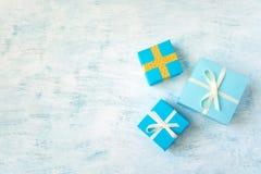 três amarelos e caixa de presente azul com fita branca e curva no ligh fotografia de stock royalty free