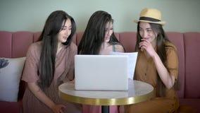 Três amigas ativas olham o cartaz relativo à promoção e escolhem a roupa nova na loja em linha que sorriem e rindo tenha a utiliz video estoque