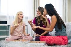 Três amigas bonitas que comem a pizza Fotografia de Stock Royalty Free