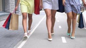 Três amigas bonitas vão ao longo da rua com pacotes após a compra e falam um com o otro Movimento lento video estoque