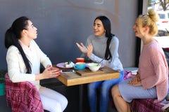 Três amigas magníficas novas da menina vibram, bisbilhotando, sha imagens de stock