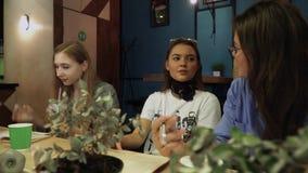 Três amigas que conversam ao sentar-se em uma tabela em um café e ao ler um livro Estilo de vida saudável de jovens filme