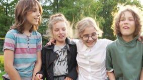 Três amigos adolescentes estão falando ao estar no parque Uma quarta amiga corre até eles Infância feliz, de volta a filme