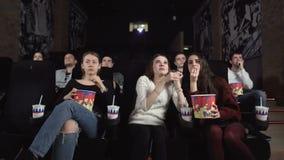 Três amigos consideravelmente fêmeas que olham um filme no cinema Homem descontentado com as meninas que falam alto video estoque