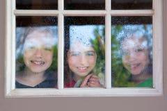 Três amigos da irmã que olham através da janela chuvosa foto de stock