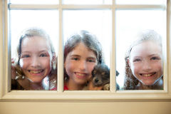 Três amigos da irmã que olham através da janela chuvosa fotografia de stock royalty free