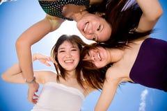 Três amigos de menina felizes que olham para baixo foto de stock royalty free