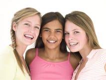 Três amigos de menina que sorriem junto Foto de Stock