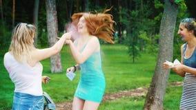 Três amigos fêmeas polvilham o pó colorido no festival das cores de Holi no parque filme