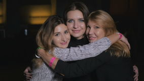 Três amigos felizes que abraçam e que olham in camera video estoque