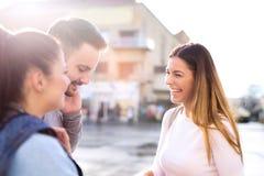 Três amigos felizes que falam tomando uma conversação na rua fotografia de stock royalty free