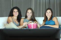 Três amigos felizes que olham a tevê foto de stock