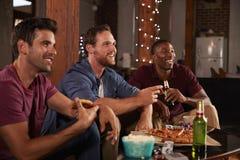 Três amigos masculinos penduram a tevê para fora de observação e pizza comer fotografia de stock