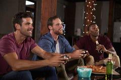 Três amigos masculinos que jogam jogos de vídeo e que bebem em casa imagem de stock royalty free