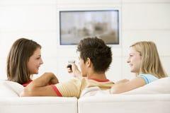 Três amigos na televisão de observação da sala de visitas imagem de stock