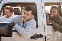 Três amigos novos do homem adulto que vão em férias em um carro foto de stock