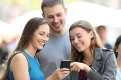 Três amigos que olham o índice dos meios no telefone imagem de stock royalty free
