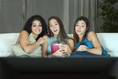 Três amigos que olham o filme romântico na tevê fotos de stock royalty free