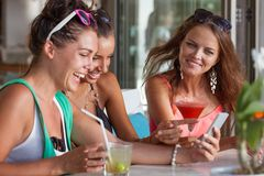 Três amigos que olham o smartphone imagens de stock