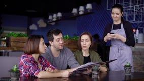 Três amigos que pedem o alimento no restaurante video estoque