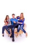 Três amigos que sentam-se em um sofá e que bebem uma soda imagem de stock
