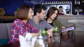 Três amigos que sentam-se na barra e que olham através do menu video estoque
