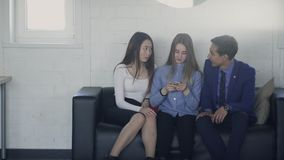 Três amigos que sentam-se no sofá no escritório e na mensagem texting no telefone video estoque