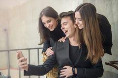 Três amigos que têm o divertimento em um café imagens de stock royalty free