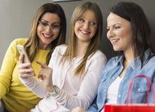 Três amigos sentam e usam um telefone celular e a emissão de mensagens de texto fotos de stock royalty free