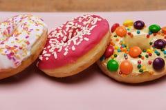 Três anéis de espuma apetitosos encontram-se em uma placa cerâmica cor-de-rosa fotos de stock