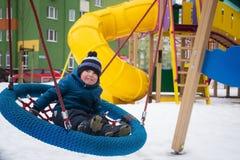 Três anos de criança que joga no campo de jogos no inverno Foto de Stock