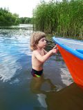 Três anos de menino idoso e um barco em uma água fotografia de stock royalty free