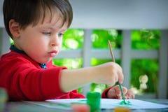 Três anos de pintura velha do menino com escova Foto de Stock Royalty Free