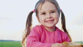 Três anos engraçados da menina, comendo um sanduíche no sol vídeos de arquivo