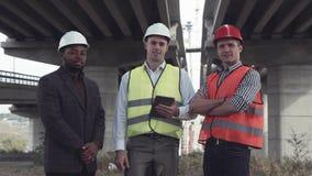 Três arquitetos nos capacetes protetores que olham a câmera Foto de Stock Royalty Free