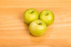 Três avó Smith Apples no contador de madeira Imagens de Stock