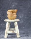 Três bacias de madeira empilhadas em um tamborete branco Imagens de Stock Royalty Free