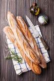 Três Baguette, azeite e alecrins franceses frescos Imagens de Stock