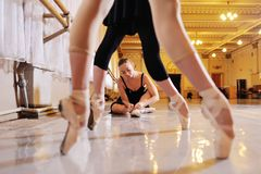Três bailarinas bonitos novas executam exercícios em uma máquina ou em uma barra coreográfica fotografia de stock royalty free