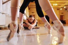 Três bailarinas bonitos novas executam exercícios em uma máquina ou em uma barra coreográfica fotos de stock