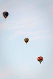 Três balões de ar quente coloridos flutuam em seguido afastado no céu Fotos de Stock